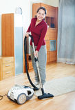 Happy mature woman cleaning with vacuum cleaner Royalty Free Stock Image