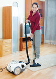 Happy mature woman cleaning with vacuum cleaner Stock Images