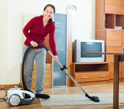 Happy mature woman cleaning with vacuum cleaner Stock Image