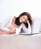 Happy mature woman with coffee cup and laptop Royalty Free Stock Photos
