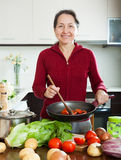 Happy mature woman cooking  with skillet Royalty Free Stock Photo