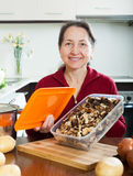 Happy mature woman with dried mushrooms Royalty Free Stock Images