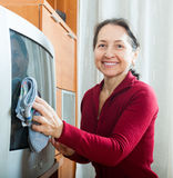 Happy mature woman dusting TV Stock Photography