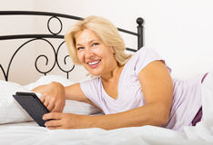Happy mature woman with eBook Stock Images