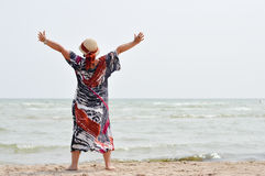 Happy mature woman enjoying breeze on seashore Stock Images