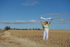Happy Mature Woman in Field of Wheat Stock Photo