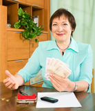 Happy mature woman with financial documents and money Stock Images