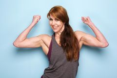 Happy mature woman flexing bicep muscles. Portrait of happy mature woman flexing bicep muscles against blue wall Stock Photos