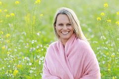 Happy mature woman in flowerfield Stock Images