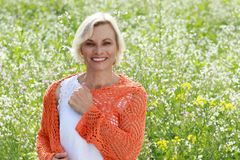 Happy mature woman in flowerfield Stock Image