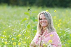 Happy mature woman  in a flowerfield Royalty Free Stock Images