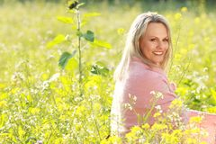 Happy mature woman  in a flowerfield Stock Image