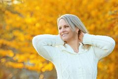 Happy mature woman in front of golden autumn leaves Stock Photo