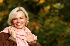 Happy mature woman in front of golden autumn leaves Royalty Free Stock Photo