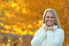 Happy mature woman in front of golden autumn leaves Royalty Free Stock Images