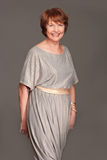 Happy  mature woman in grey dress Royalty Free Stock Images