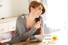 Happy mature woman having breakfast at home. Portrait of happy mature woman enjoying having breakfast at home and smiling Royalty Free Stock Photos