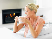 Happy mature woman having a cup of coffee Stock Images