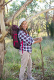 Happy Mature woman hiking with backpack and stick stock image