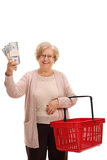Happy mature woman holding bundles of money and shopping basket Stock Image