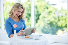 Happy mature woman holding digital tablet Stock Images