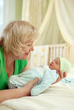 Happy mature woman holding her newborn grandson Royalty Free Stock Photo
