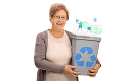 Happy mature woman holding recycling bin full of plastic bottles Stock Image