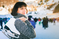 Happy mature woman holds skates at Medeo ice rink Stock Image