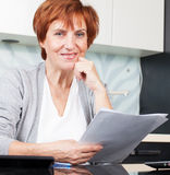 Happy mature woman on kitchen with documents Stock Photography