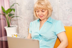 Happy mature woman with laptop at home. Portrait of happy mature woman with laptop at home royalty free stock photography