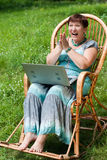 Happy mature woman with laptop in rocking chair. Hand clapping excited Stock Images