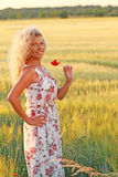 Happy mature woman with a long dress in summer evening. In front of a corn field stock photography