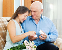 Happy mature woman looking jewel  from husband Royalty Free Stock Photos