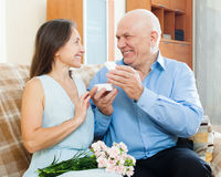 Happy mature woman looking jewel  from  man Stock Images