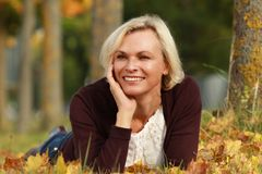 Happy mature woman in front of golden autumn leaves Royalty Free Stock Photography