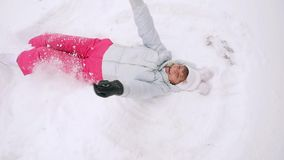 Happy mature woman lying in snowdrift enjoying snowfall in slowmotion. 1920x1080 stock footage