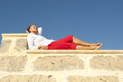 Happy mature woman lying on wall Stock Image