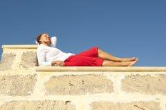 Happy mature woman lying on wall Stock Image