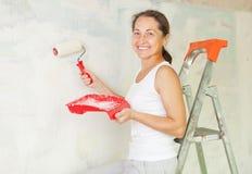 Happy mature woman makes repairs Stock Image