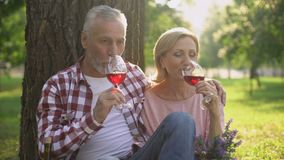 Happy mature woman and man drinking wine and enjoying romantic date in park