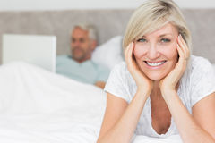 Happy mature woman with man using laptop in bed Stock Photography