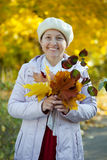 Happy mature woman with maple posy Royalty Free Stock Images
