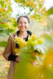 Happy mature woman with maple posy. Outdoor portrait of  happy mature woman with maple posy Royalty Free Stock Images