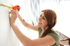 Happy mature woman marking wall. Portrait of happy mature woman making a mark on white wall with measure tape and pencil Royalty Free Stock Photo