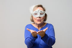 Happy mature woman in mask with open hands. Holding nothing over neutral gray background Royalty Free Stock Image