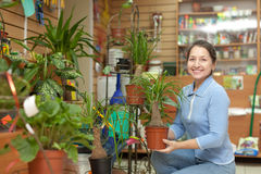 Happy mature woman with Nolina plant Royalty Free Stock Photos