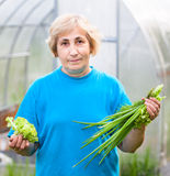 Happy mature woman with onion and lettuce Royalty Free Stock Images