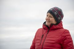 Happy mature woman outdoors on a cold day royalty free stock photography
