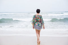 Happy mature woman with outspread arms Enjoying Vacation. Happy healthy mature woman walking, Enjoying freedom on the Ocean Beach. Travel Vacation. Wellness and Royalty Free Stock Photo
