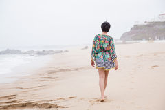 Happy mature woman with outspread arms Enjoying Vacation. Happy healthy mature woman walking, Enjoying freedom on the Ocean Beach. Travel Vacation. Wellness and Royalty Free Stock Photos